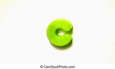 Green letter c lifting off white background in slow motion