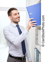 handsome businessman picking folder at office - business and...