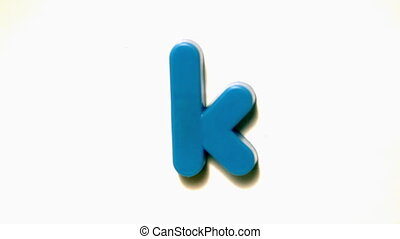 Blue letter k lifting off white background in slow motion