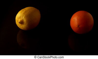 Lemon and orange spinning on black surface in slow motion