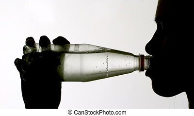 Silhouette of woman drinking from bottle in slow motion