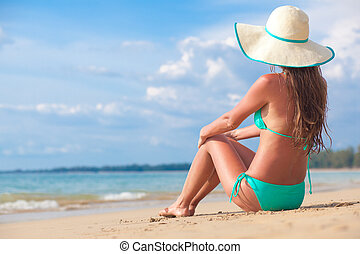 long haired girl in bikini and straw hat on tropical beach