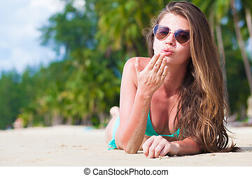 front view of long haired young woman in bikini lying on...