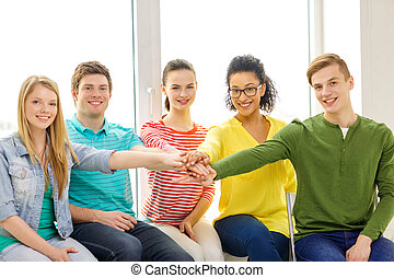 smiling students with hands on top of each other