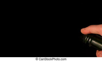 Hand popping champagne cork on black background in slow...