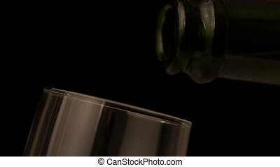Champagne pouring into flute on black background in slow...