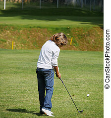 Young golfer performs a golf shot