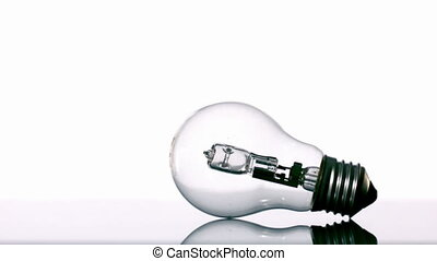 Hammer smashing light bulb on white background in slow...