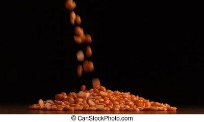 Peanuts pouring on black background in slow motion