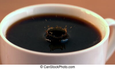 Drop falling into cup of coffee