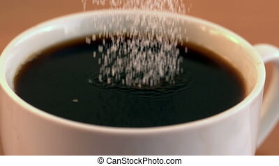 Sugar pouring into cup of coffee in slow motion