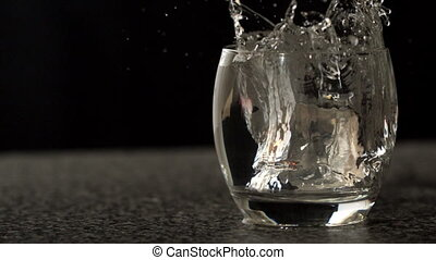 Ice cube falling into glass of water in slow motion