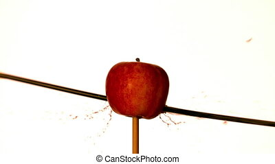 Arrow shooting through red apple on white background in slow...