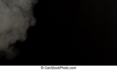 Smoke blowing against black background