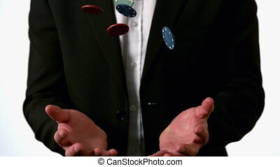 Man in suit catching falling casino chips - Man in suit...