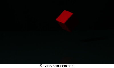 Red block spinning on black surface in slow motion