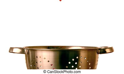 Pepper slices falling into colander in slow motion