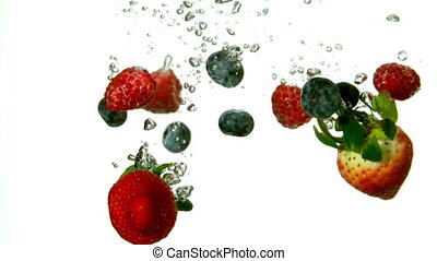 Berries falling in water on white background