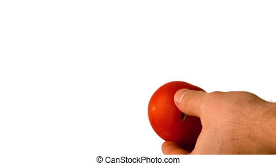 Hand throwing tomato and halving it with knife in slow...