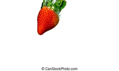 Strawberry falling in water on white background in slow...