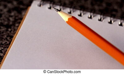Pencil falling on a notepad in slow motion