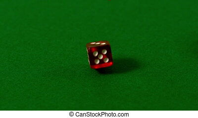 Red dice falling on casino table in slow motion