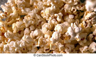 Salty popcorn pouring onto more in slow motion