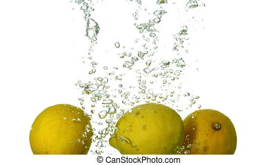Lemons plunging into water on white background in slow...