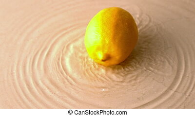 Lemon spinning on wet white surface in slow motion