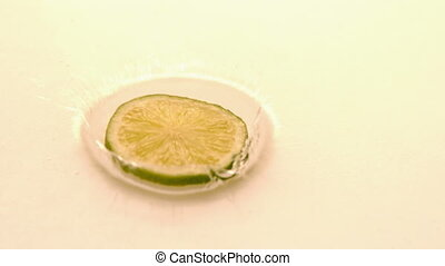 Slice of lime falling on white wet surface