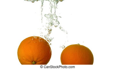 Oranges plunging into water on white background in slow...