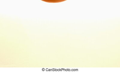 Orange falling and bouncing on white wet surface in slow...