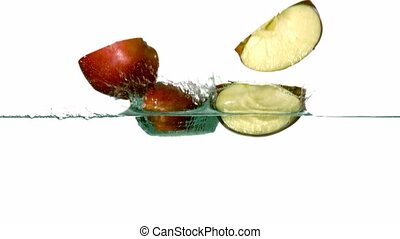 Apple segments plunging into water on white background in...