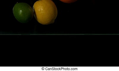 Lemon orange and lime plunging into water on black...