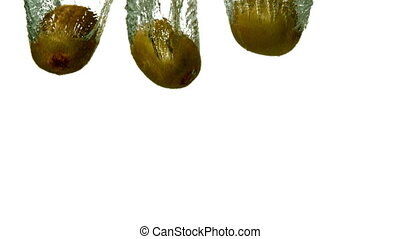 Three kiwi fruits plunging into water on white background in...