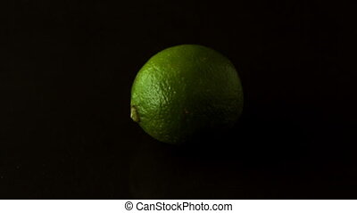 Lime spinning on black surface in slow motion