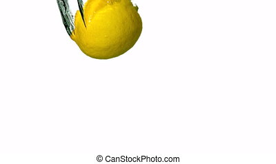 Lime and lemon plunging into water on white background in...