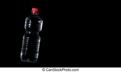 Plastic bottle spinning on black surface in slow motion