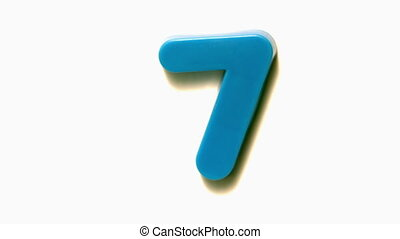 Blue number seven lifting off white background in slow...