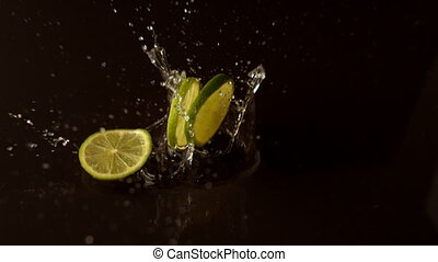 Lime slices dropping on wet black surface in slow motion