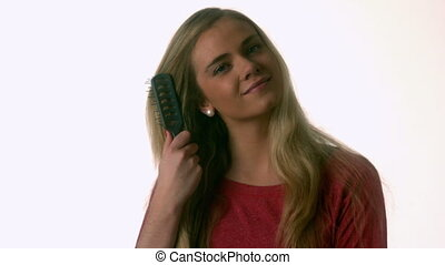 Pretty blonde brushing her hair in slow motion