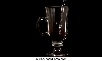 Hot water pouring over coffee granules in a glass in slow...