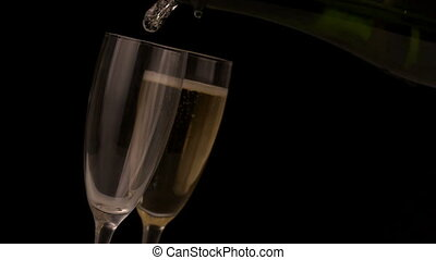 Champagne pouring into flutes on black background in slow...