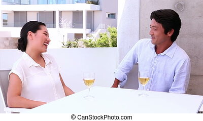 Asian couple having white wine together outside on a balcony
