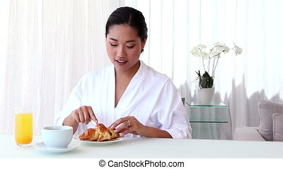 Asian woman having breakfast in bathrobe at home in the...