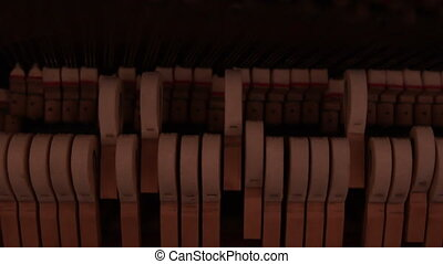 Piano hammers hitting strings in slow motion