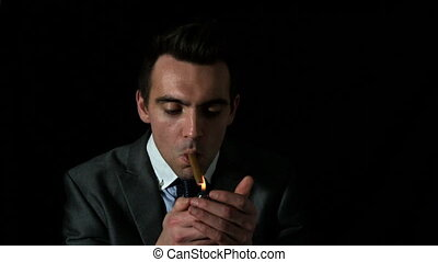 Businessman lighting his cigar on black background in slow...