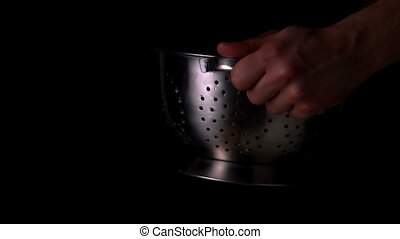 Hands tossing spaghetti in colander in slow motion