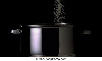 Rice pouring into pot on black background in slow motion
