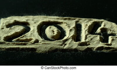 2014 spelled out in sand blowing away in slow motion